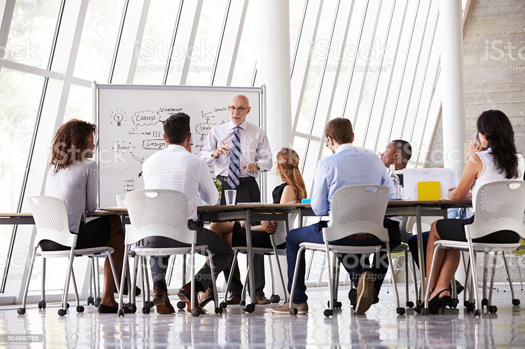 Senior Businessman Leading Meeting At Boardroom Table stock photo