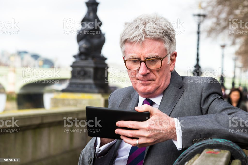 Senior businessman looking at his digital tablet in central London, UK stock photo