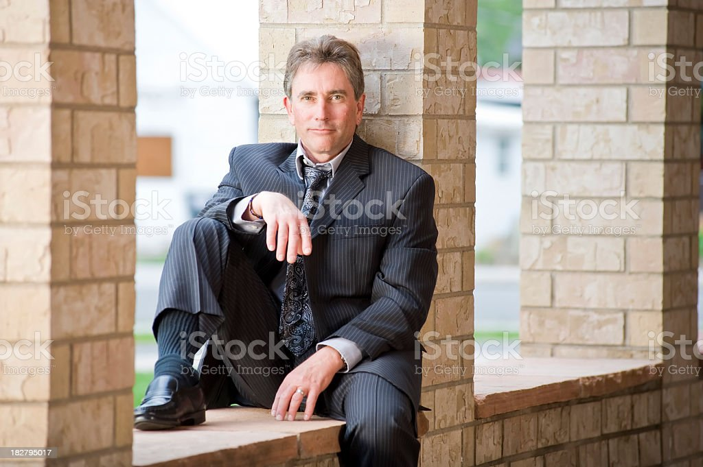 Senior Businessman looks into camera while resting after long day stock photo