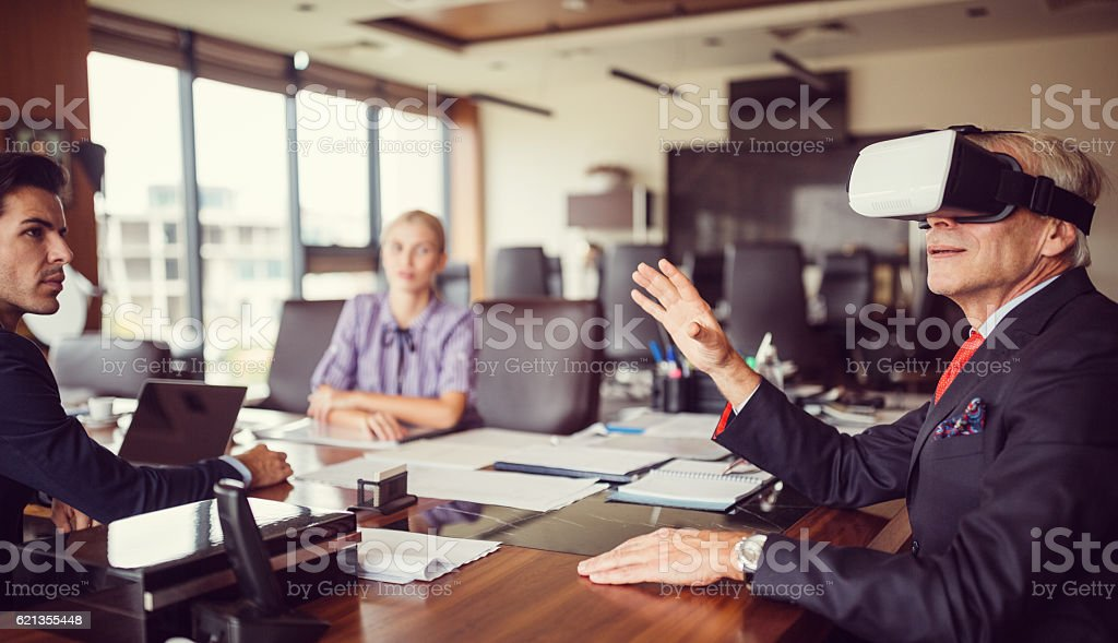 Senior businessman presenting virtual reality simulator at business meeting stock photo