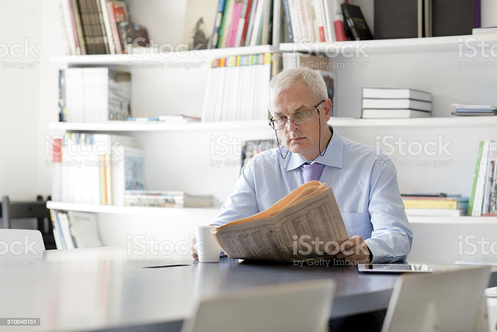 Senior businessman reading newspaper in office. stock photo