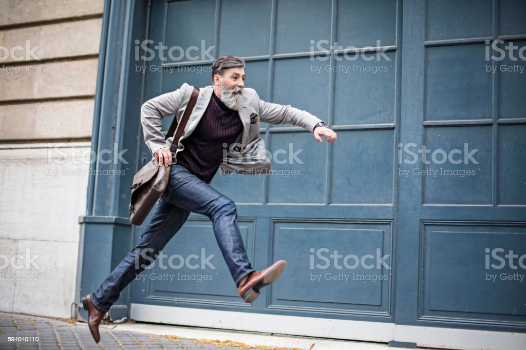 Senior businessman rushing around the city stock photo