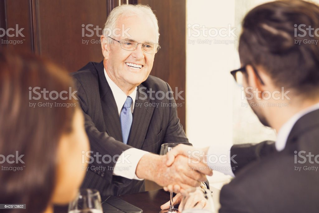 Senior Businessman Shaking Hands with Partners stock photo
