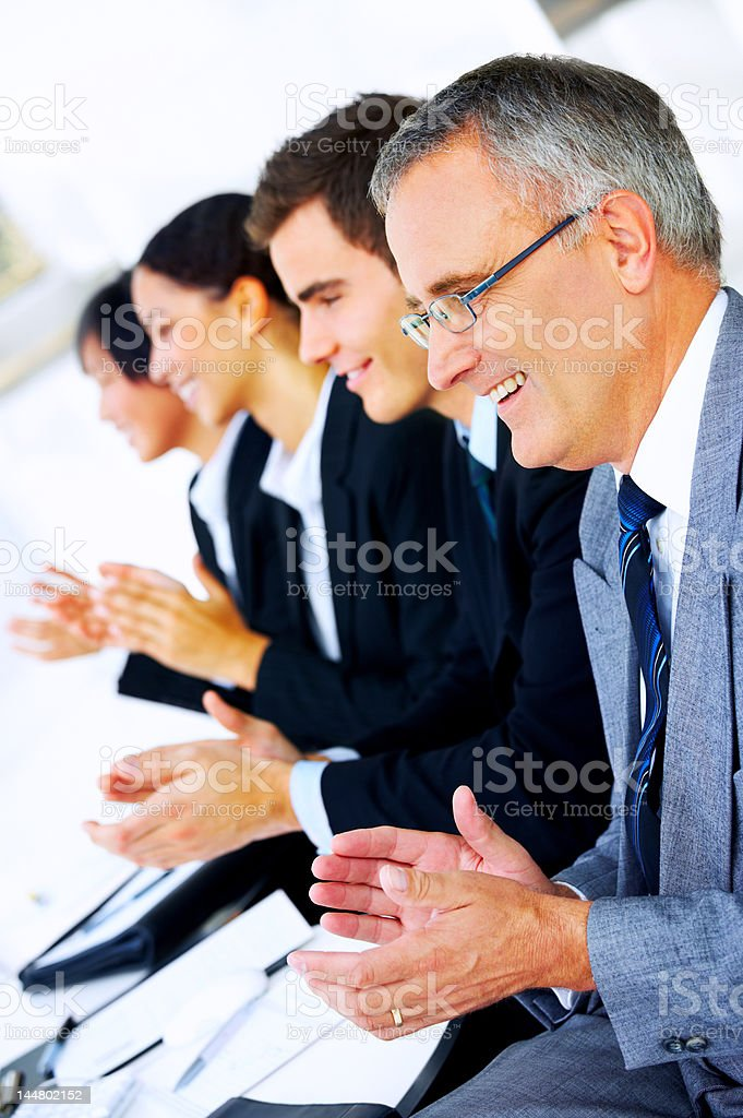 Senior businessman sitting at a meeting amidst his colleagues royalty-free stock photo