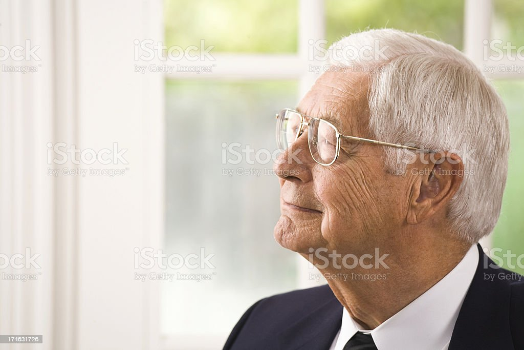 senior businessman, sitting in executive chair, looking away royalty-free stock photo