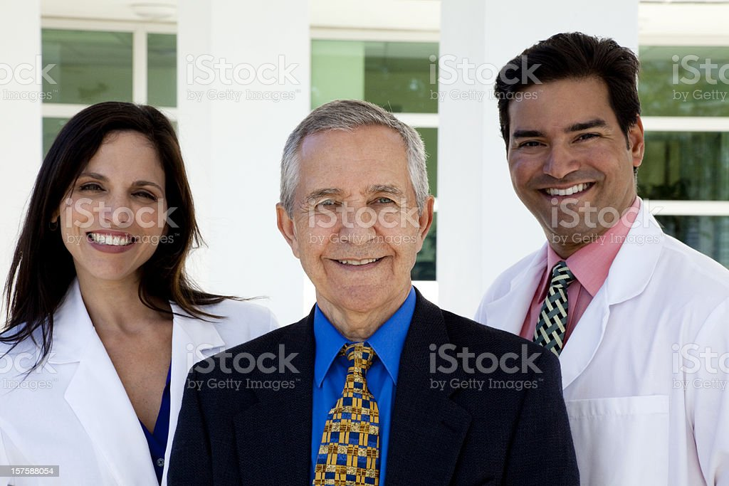 Senior businessman standing with female and male wearing lapcoats stock photo