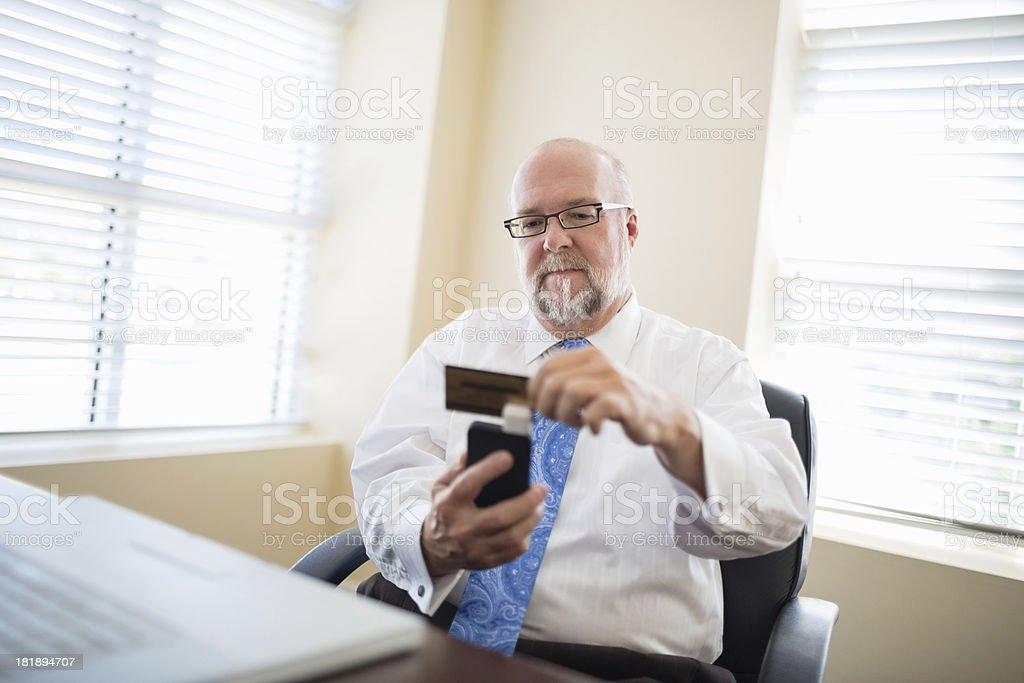 Senior Businessman Swiping Credit Card stock photo