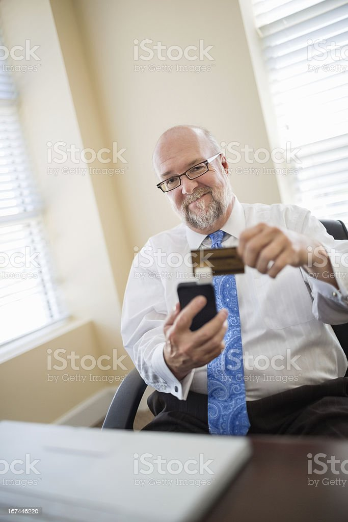 Senior Businessman Swiping Credit Card Using Reader stock photo