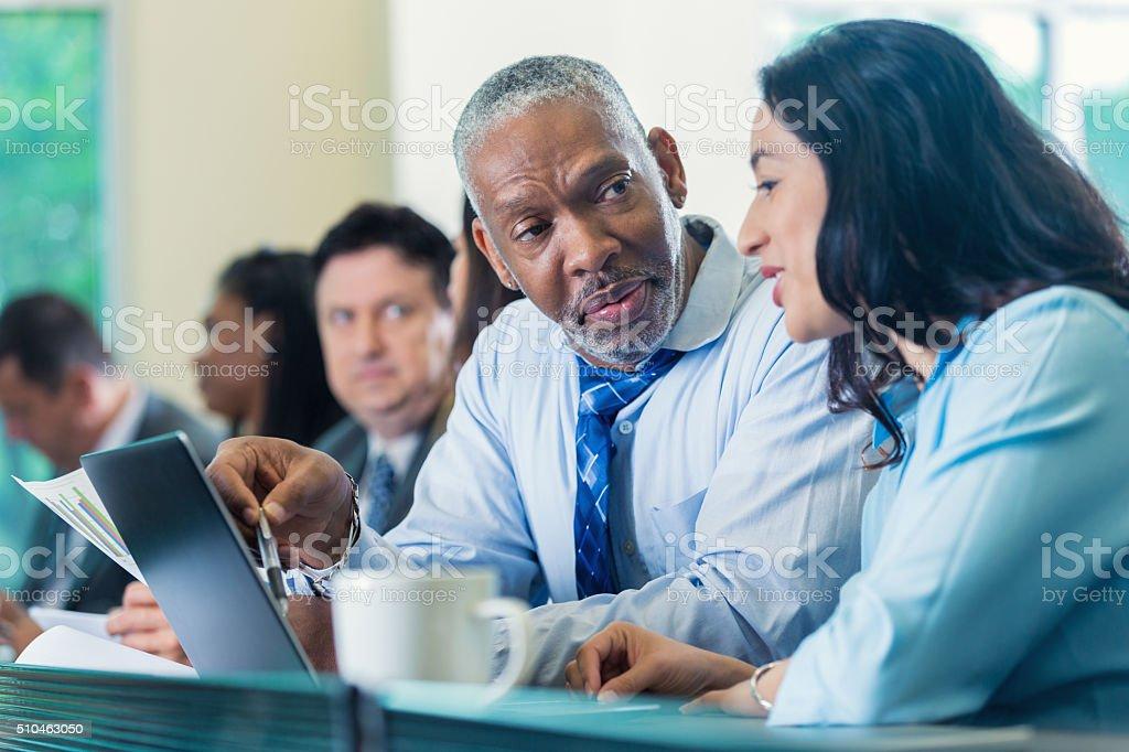 Senior businessman talking with colleague at seminar stock photo