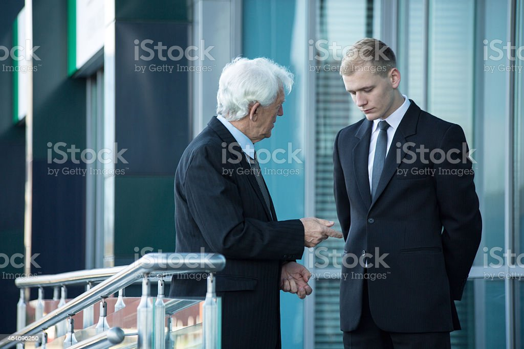 Senior businessman talking with his employee stock photo
