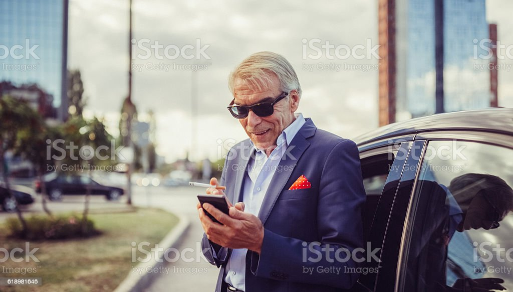 Senior businessman texting in the city stock photo