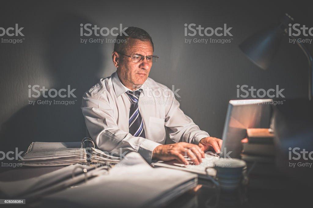 Senior businessman typing on laptop stock photo
