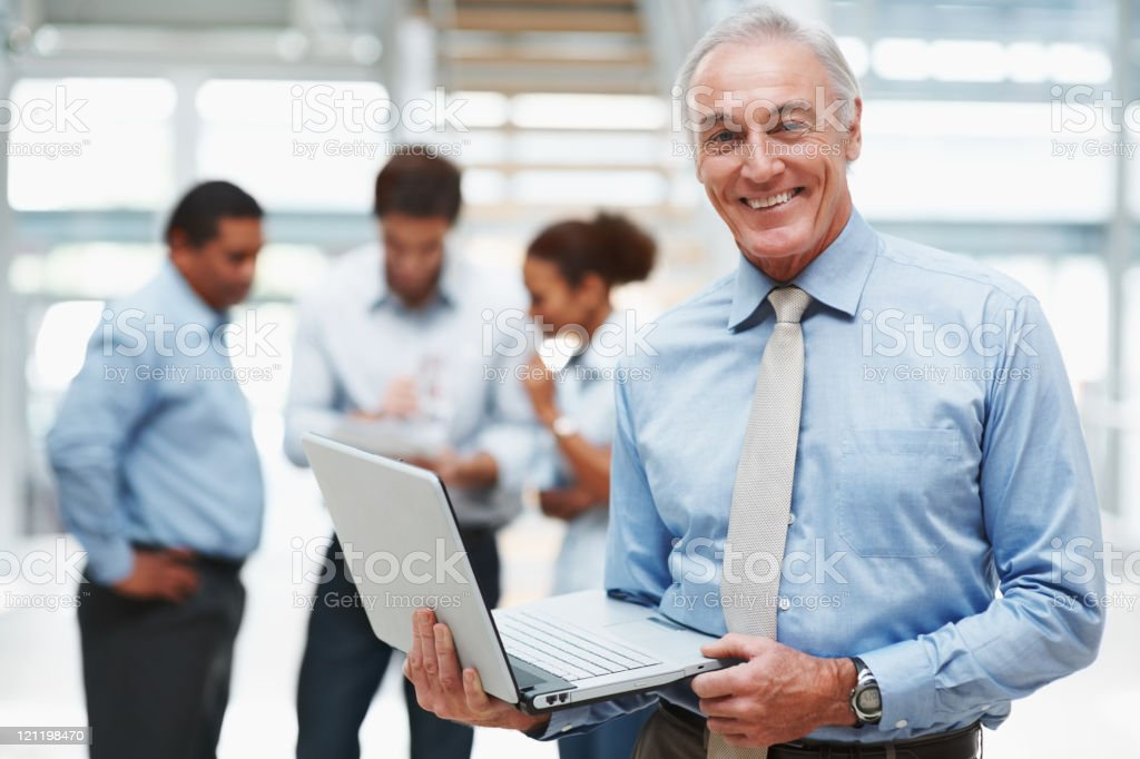 Senior businessman using a laptop with colleagues at the back stock photo