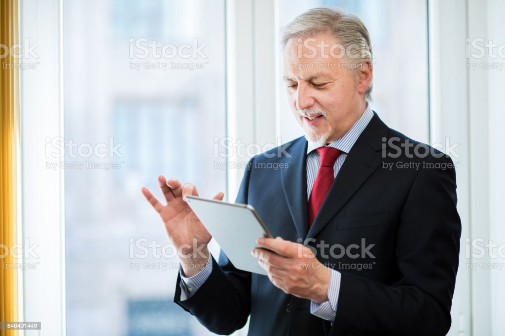 Senior businessman using a tablet stock photo