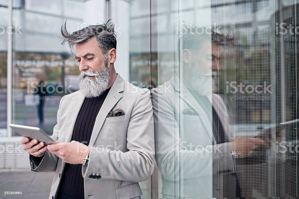 Senior businessman using digital tablet in office building stock photo
