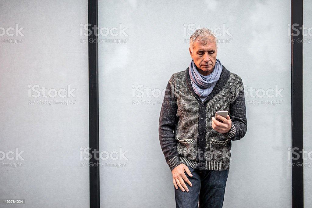 Senior businessman using mobile phone against curtain wall. stock photo