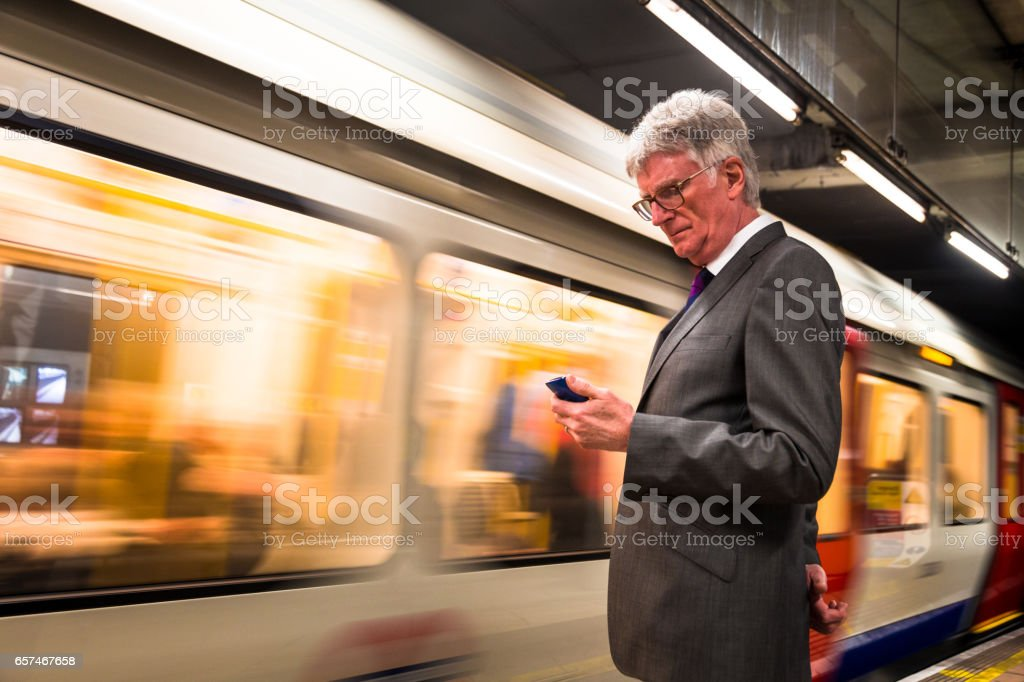 Senior businessman waiting for an underground tube train looking at his mobile phone, London, UK stock photo