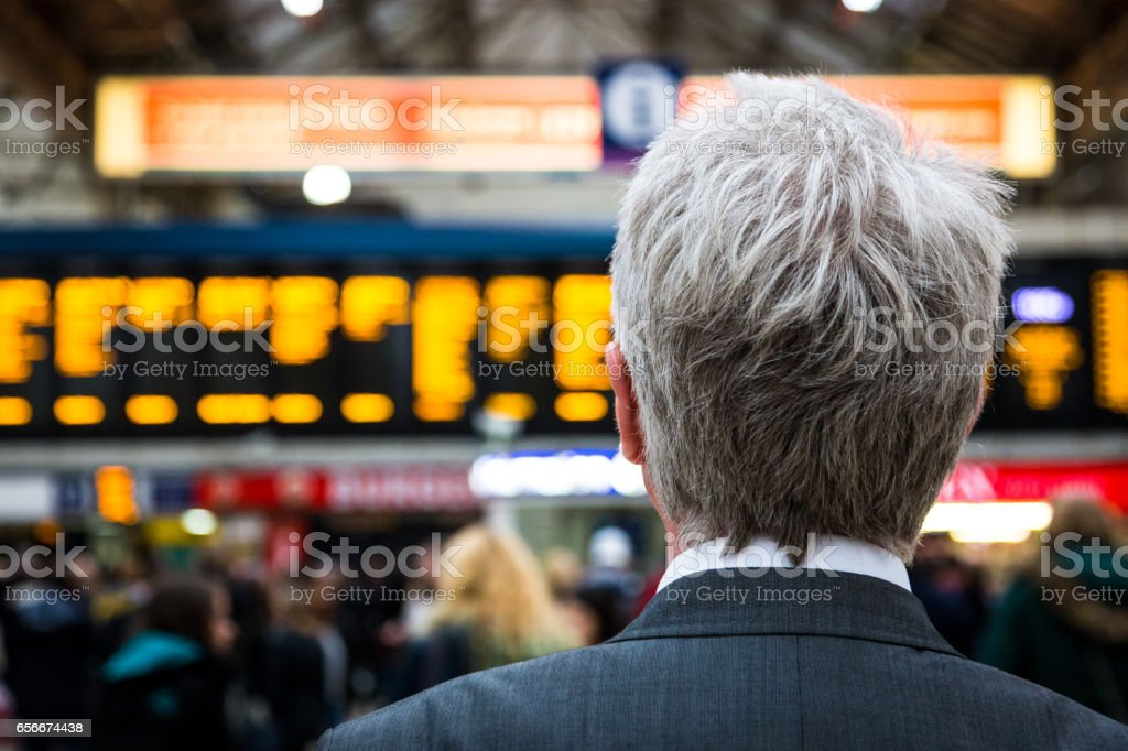 Senior businessman waiting for train with departure boards in background, London, UK stock photo