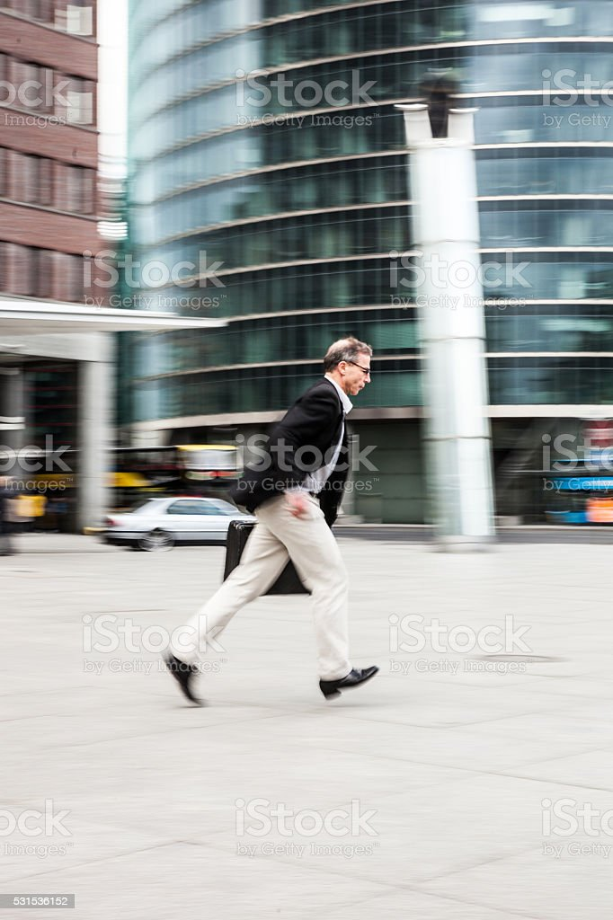 Senior businessman walking in the city streets stock photo