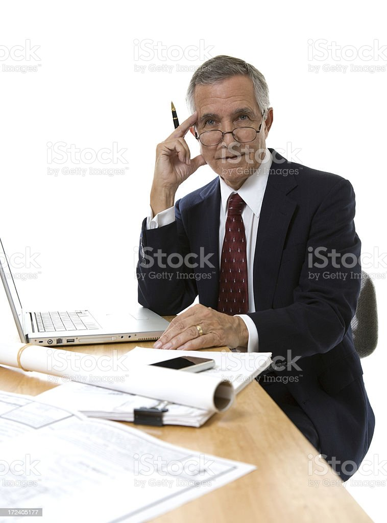 Senior businessman wearing glasses sitting at desk with papers stock photo