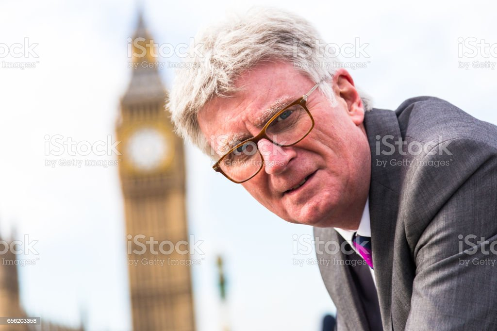 Senior businessman wearing suit and spectacles on Westminster Bridge, London, UK stock photo
