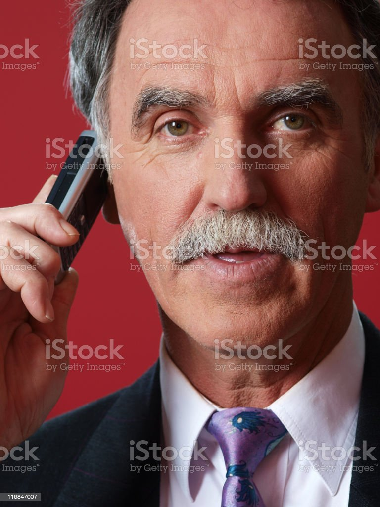 Senior businessman with mobile phone looking at camera royalty-free stock photo