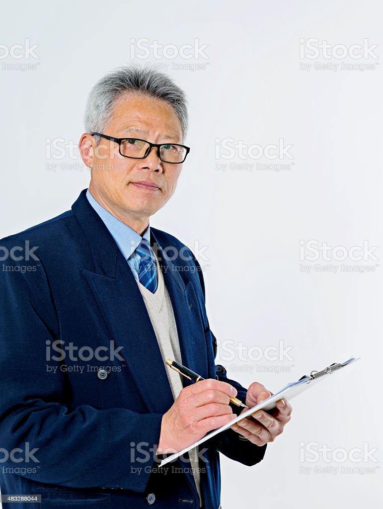 Senior businessman writing on a clipboard stock photo