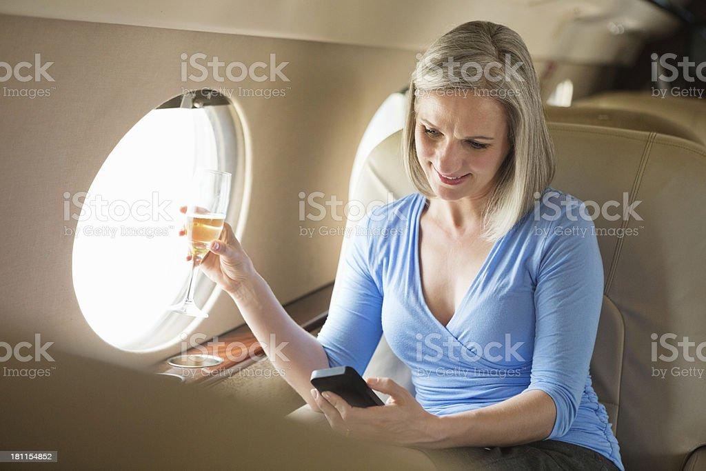 Senior businesswoman drinking champagne on board private jet stock photo