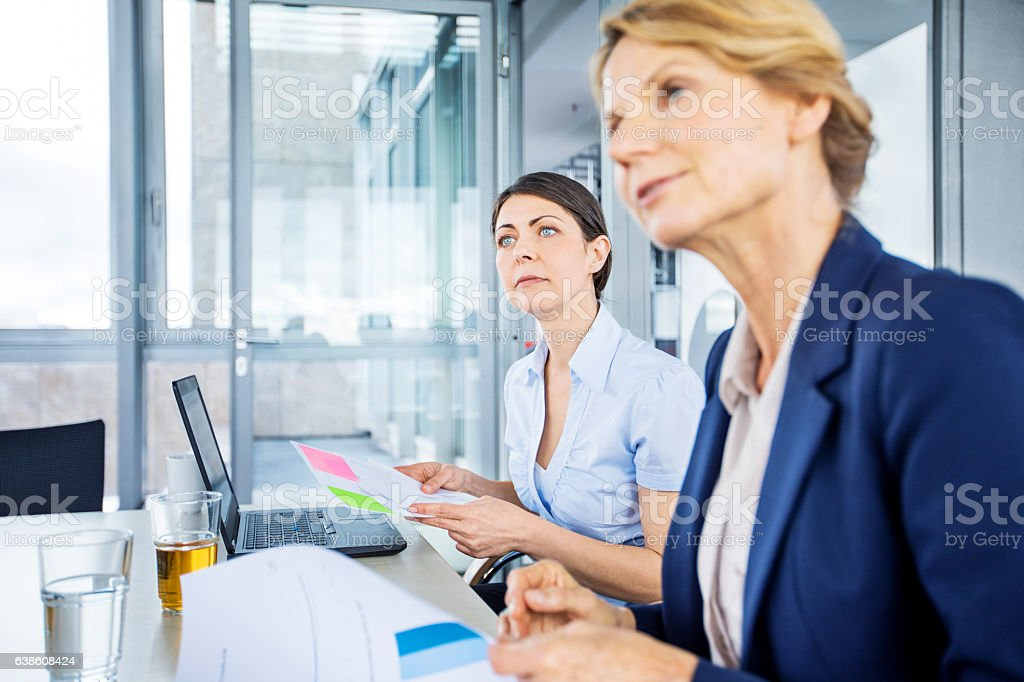 Senior businesswoman sitting attentively during meeting stock photo