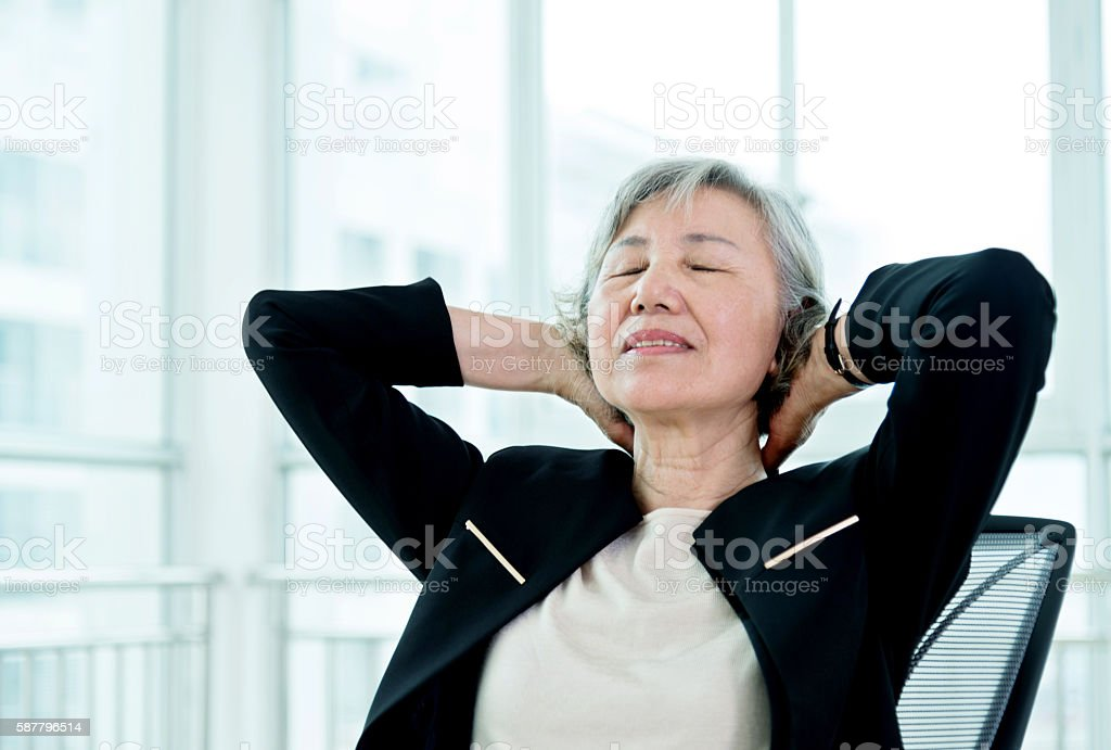 Senior businesswoman taking a break from work at the office stock photo