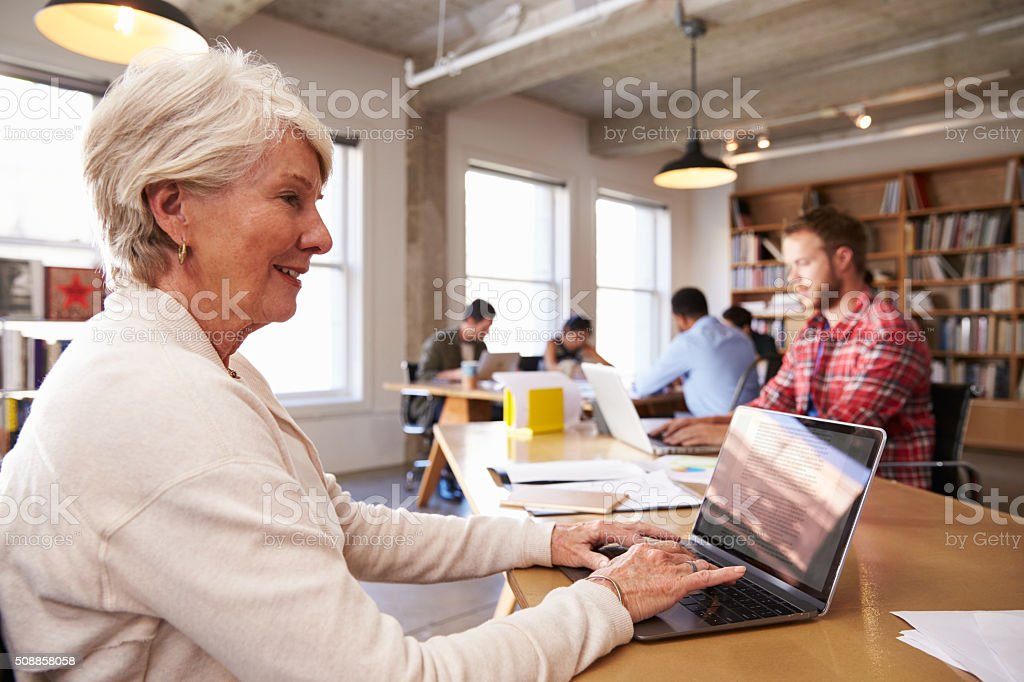 Senior Businesswoman Using Laptop At Desk In Busy Office stock photo