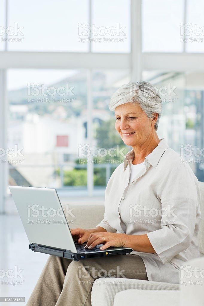 Senior businesswoman using laptop at home royalty-free stock photo