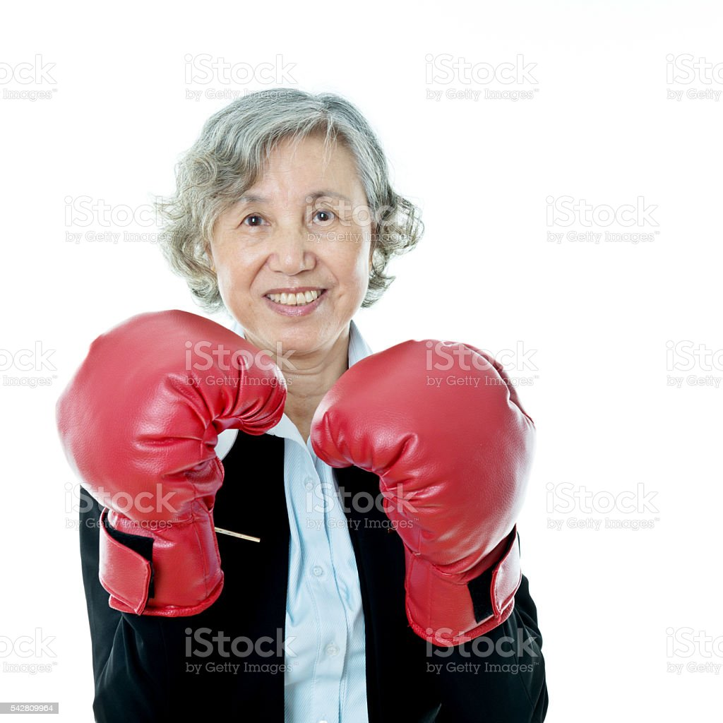 Senior businesswoman with boxing gloves stock photo