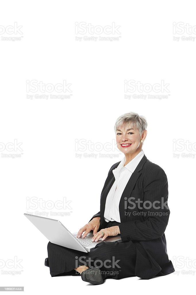 Senior Businesswoman With Laptop While Sitting On Floor stock photo