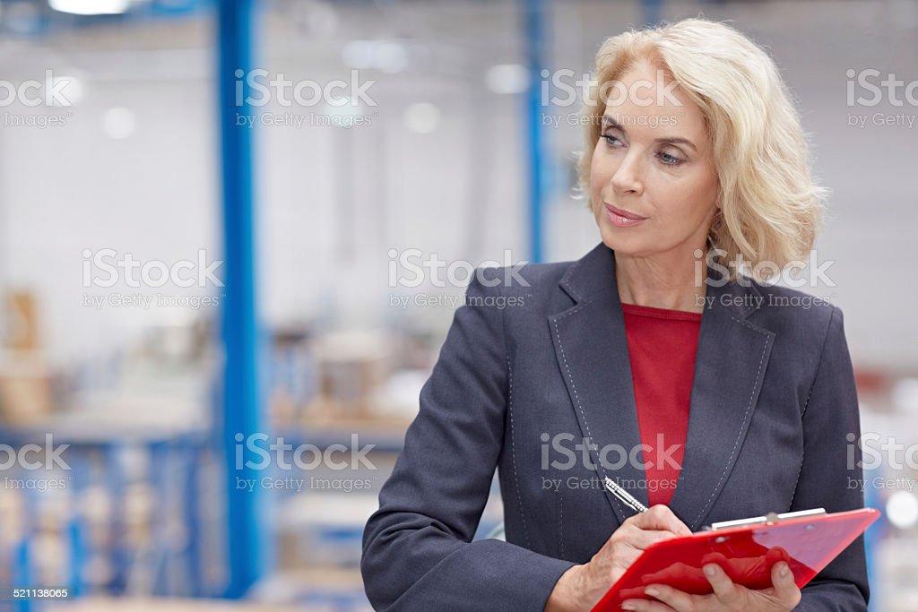 Senior businesswoman writing inventory stock photo