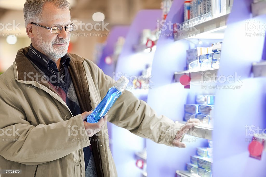 senior  buying cosmetics, for oral hygiene   in the supermarket stock photo