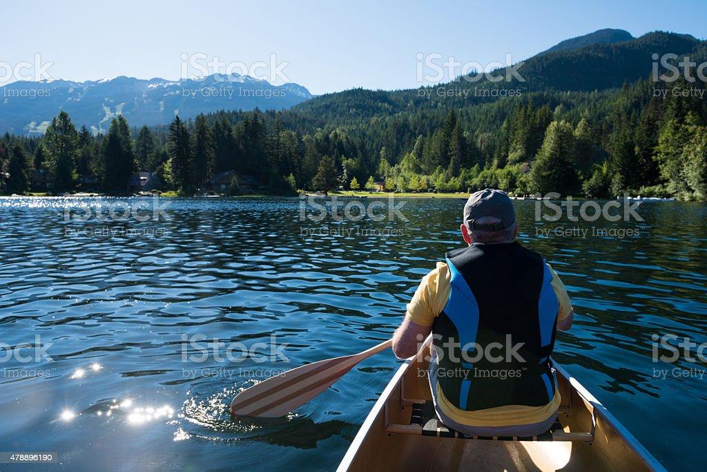 Senior canoeing on a pristine lake stock photo