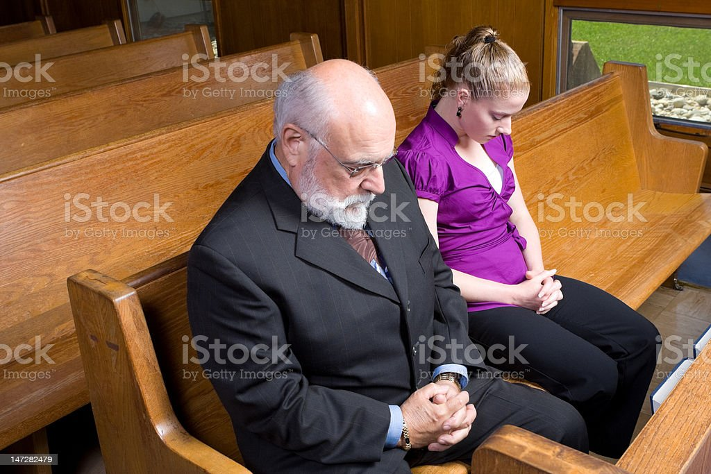 Senior Caucaisan Man and Young Woman Praying in Church Pew royalty-free stock photo