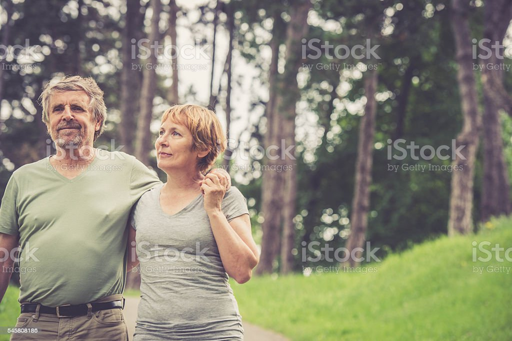 Senior caucasian couple hugging and walking outdoors in city park stock photo