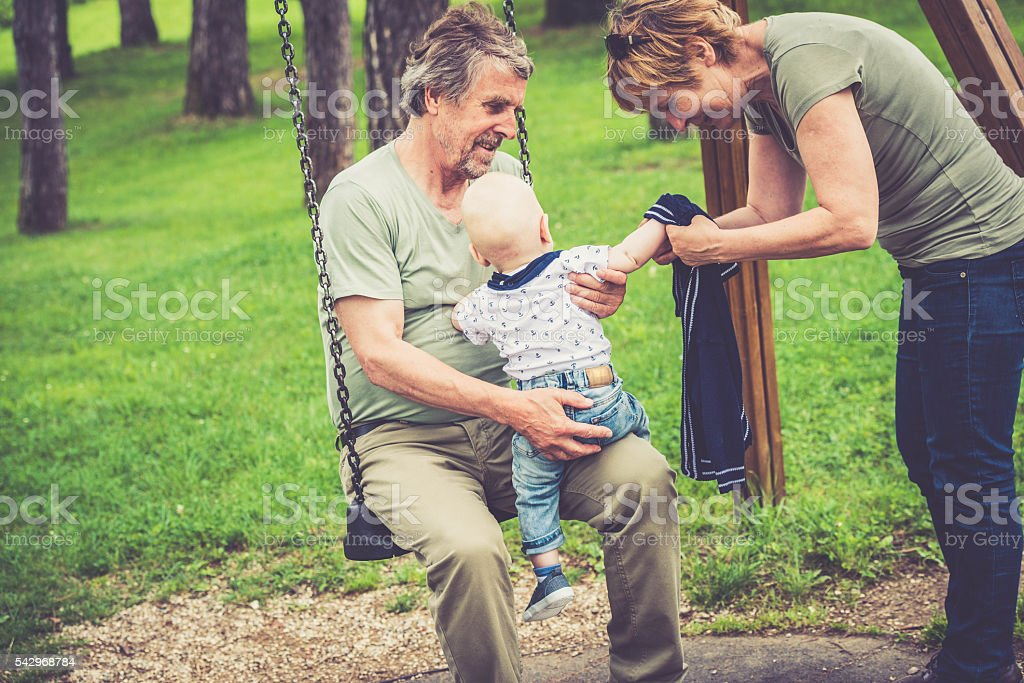 Senior caucasian couple outdoors dressing their grandson in city park stock photo