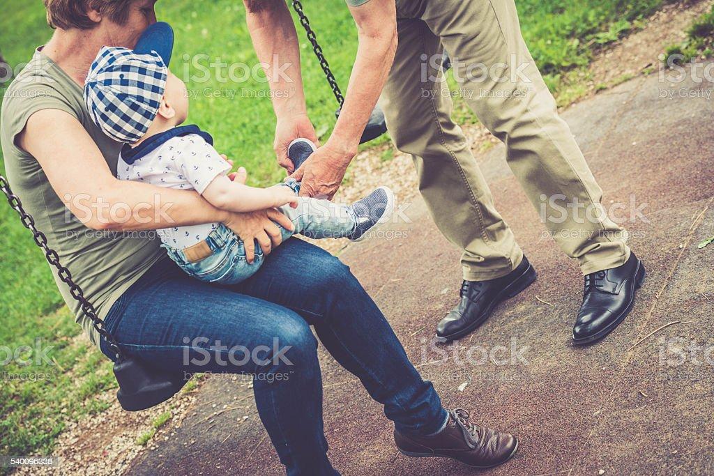 Senior caucasian couple putting on shoes to their grandson stock photo