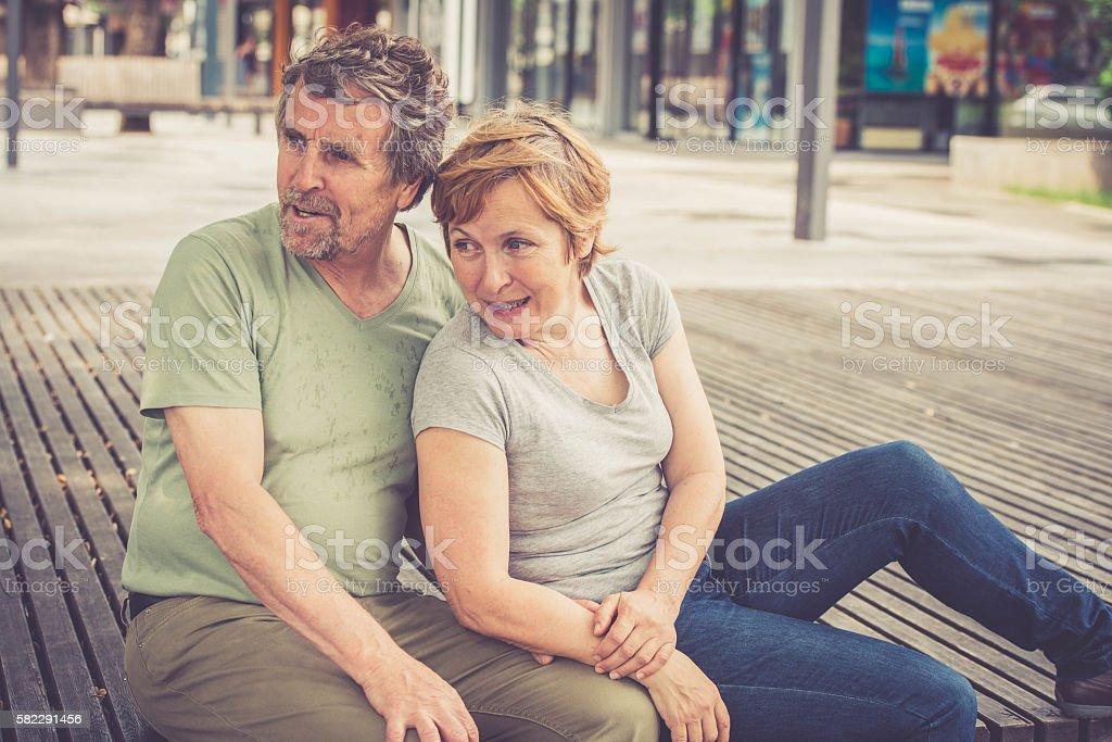 Senior caucasian couple sitting in the city center stock photo