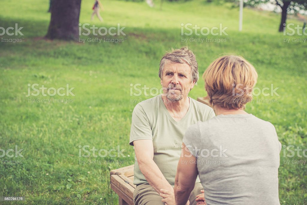 Senior caucasian couple smiling, talking and holding hands outdoors stock photo