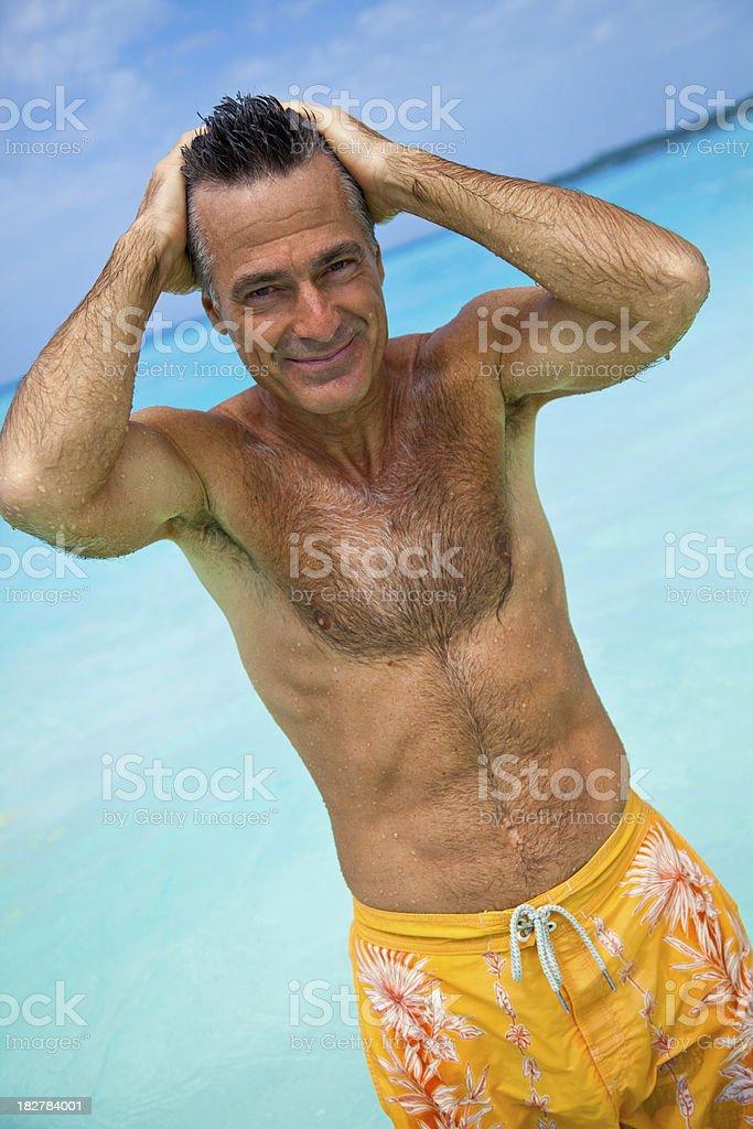 Senior caucasian man in swimwear walking out of the ocean royalty-free stock photo