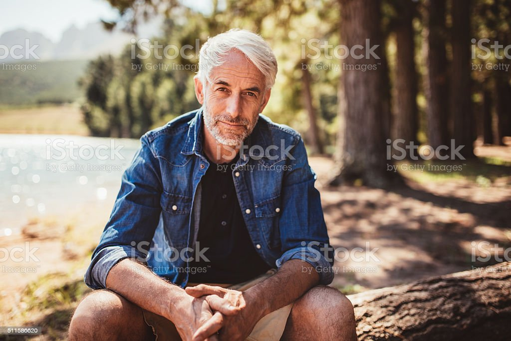 Senior caucasian man relaxing on a log by the lake stock photo