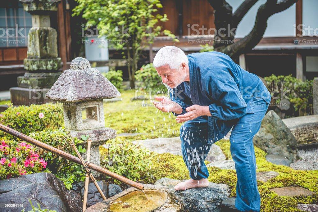 Senior Caucasian Man Washing in Buddhist Temple Garden, Kyoto, Japan stock photo