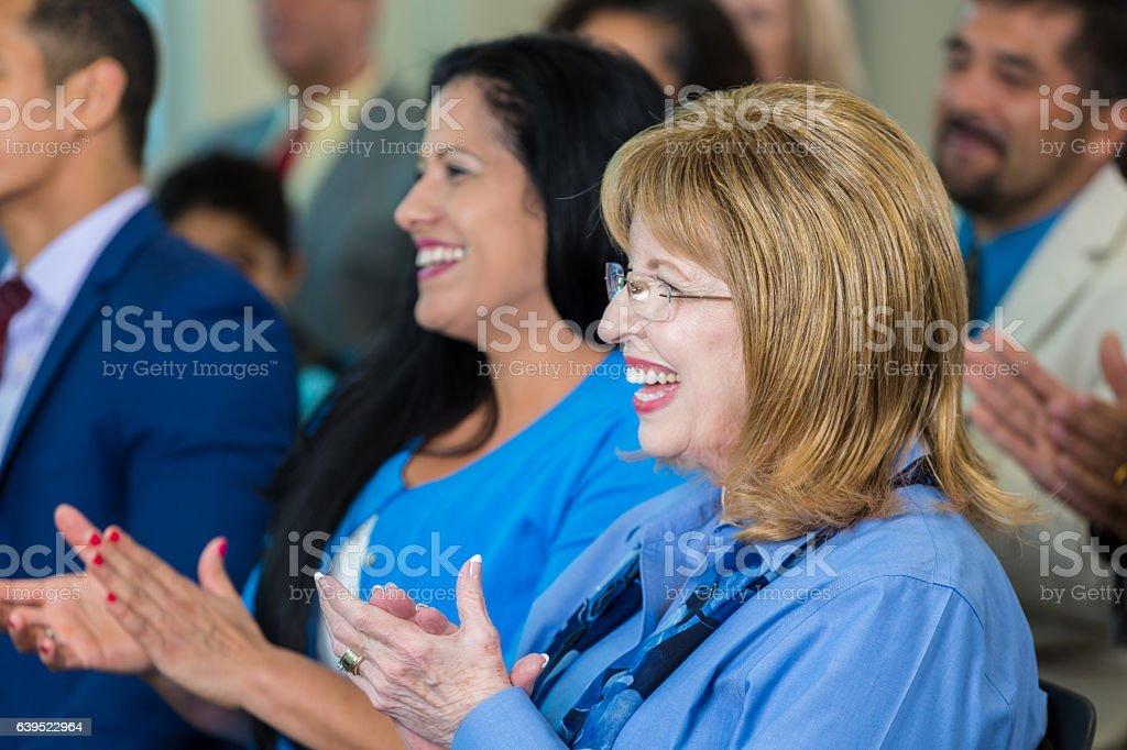 Senior Caucasian woman applauds during town hall meeting stock photo