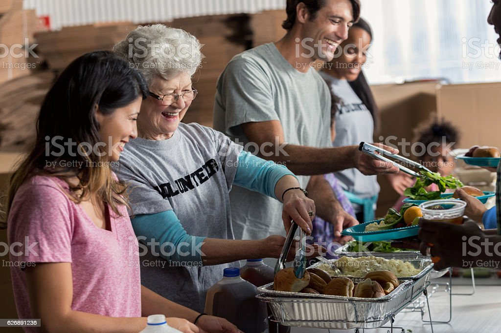 Senior Caucasian woman serves meal in soup kitchen stock photo