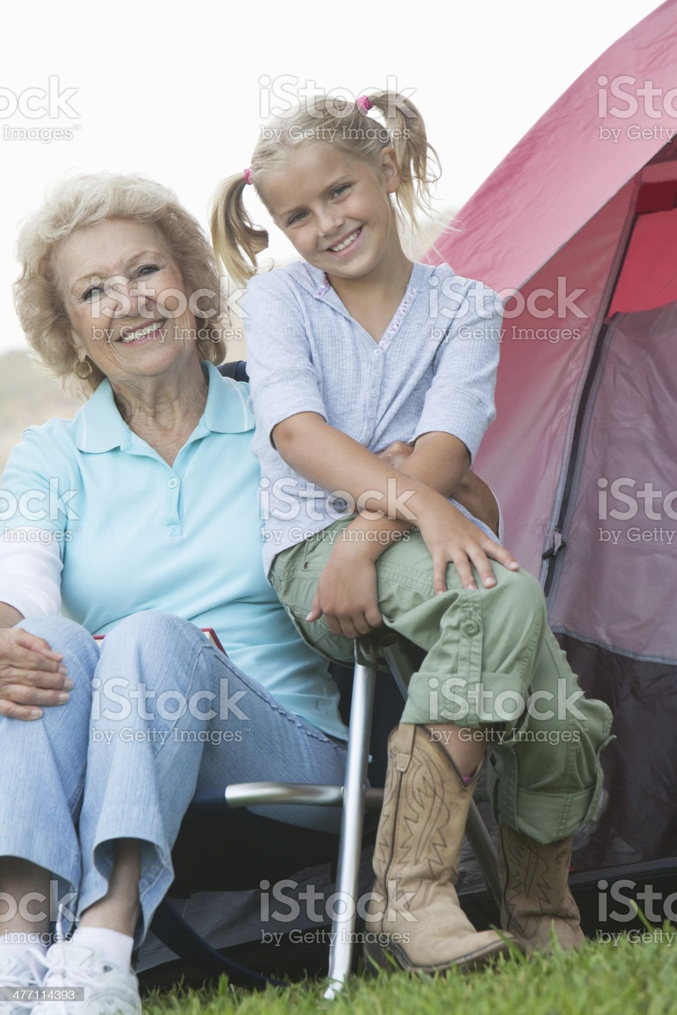 Senior Caucasian woman with granddaughter sitting outside tent royalty-free stock photo