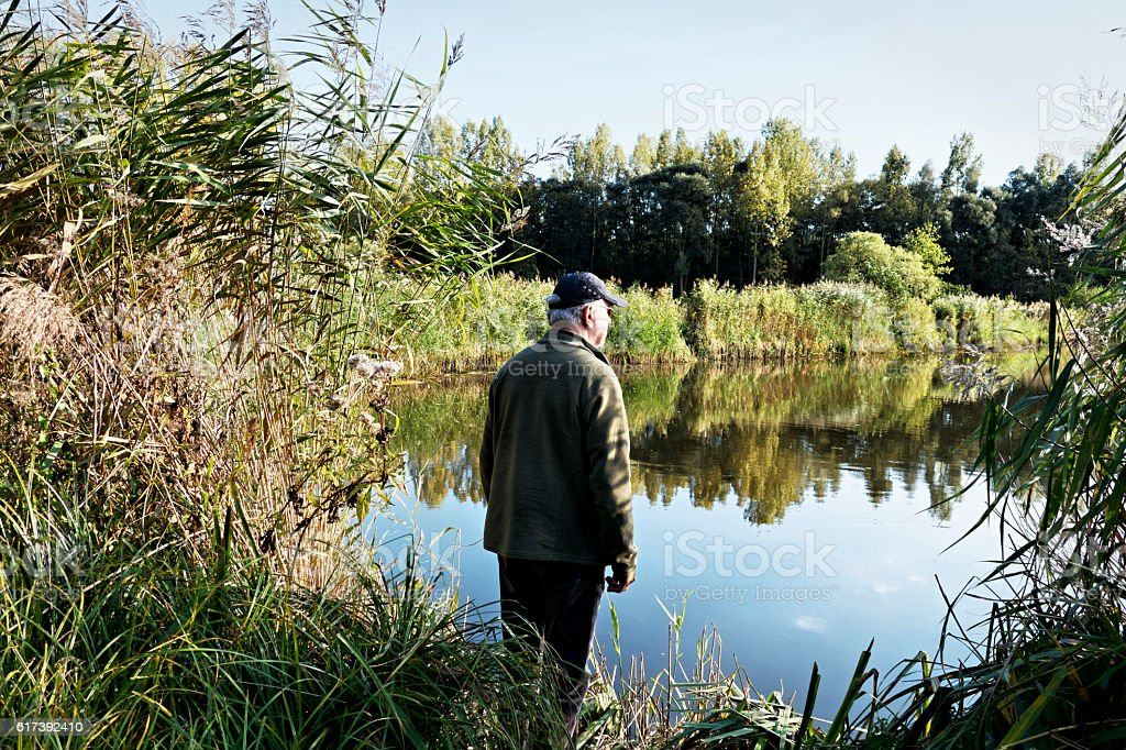 Senior causasian man standing at the edge of the water stock photo